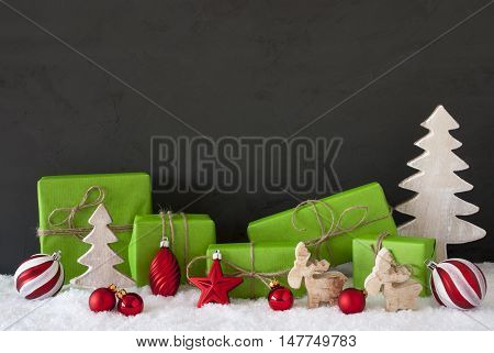 Green Gifts Or Presents With Christmas Decoration Like Tree, Moose Or Red Christmas Tree Ball. Black Cement Wall As Background With Snow. Christmas Greeting Card