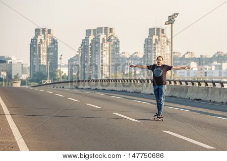 Skateboarder Riding A Skate Over A City Road Bridge. Free Ride Skateboards