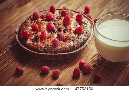Fruit cake and cup of milk on the table. Fresh sweet cake with berries and a large cup of milk is on the table. Fresh fruit harvest. Sweet dessert and cup of milk on a wooden table.