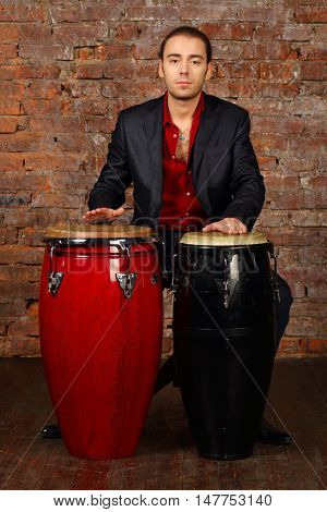 Handsome young man in suit hits drums in studio with brick wall