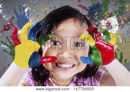 Beautiful little girl smiling at the camera while showing her hands painted in colorful