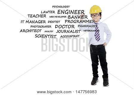 Picture of a little boy writing his dream jobs while wearing helmet isolated on white background