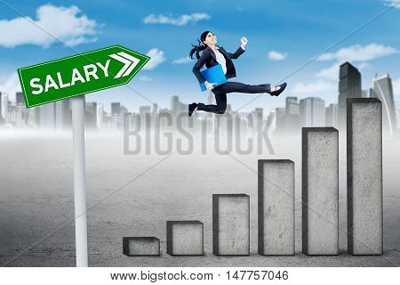 Growing salary concept. Young businesswoman running above salary chart with salary text on the signpost