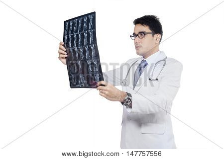 Young doctor holding x-ray or roentgen image while checking the results isolated on white background
