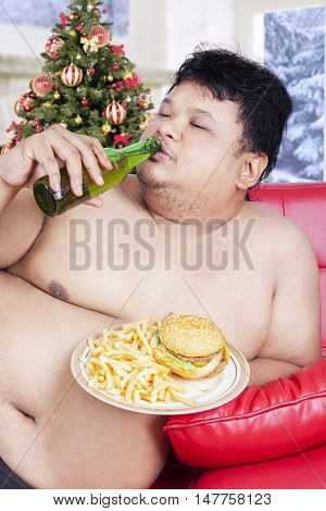 Portrait of lazy overweight man sitting on the sofa while enjoying fresh beer and fast food at christmas day