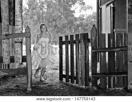 Young bride wearing gumboots under her wedding dress running through a farm gate