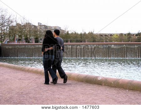 Couple Strolling In City Park