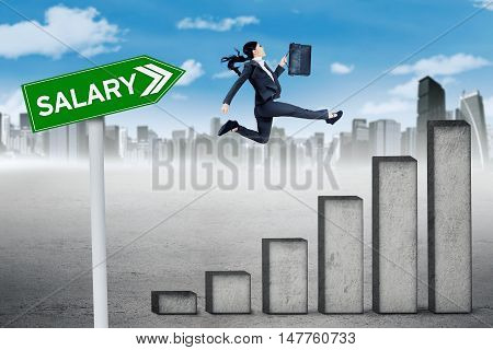 Growing salary concept. Female worker jumping above a growing salary chart with a salary word on the signpost