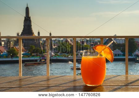 Orange juice on table in rooftop bar with famous place background. Wat Arun Bangkok Thailand
