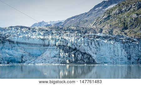 John Hopkins Glacier in Glacier Bay National Park and Preserve in Southeast Alaska is twelve miles long with layers of rock debris mixed with ice.
