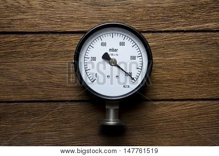 pressure gauge on old wood background, top view