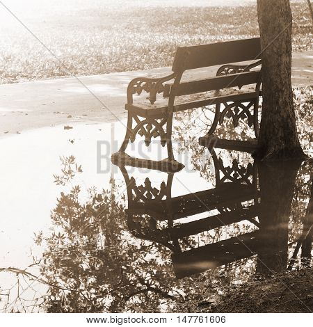 Empty bench in the park after raining sepia color tone