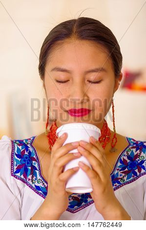 Headshot pretty young woman wearing traditional andean blouse, drinking coffee from white mug.