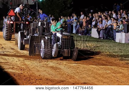 MYERSTOWN, PENNSYLVANIA - SEPTEMBER 16, 2016: A young boy drives a modified lawn tractor at Myerstown East End Days. The tractor pull is an annual community event.