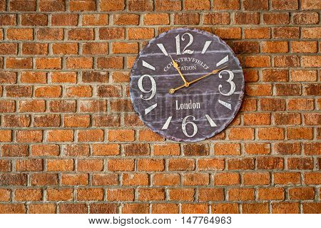 Vintage clocks at the brick wall retro background
