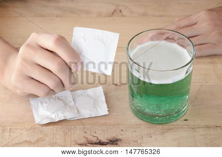 woman put effervescent tablet in glass of water on wooden table