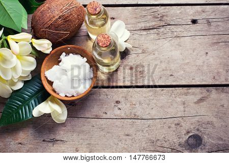 Spa set with coconuts. Coconuts and coconut oil on vintage wooden background. Natural organic spa products. Place for text. Toned image.