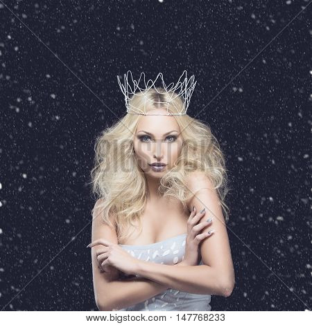 Beautiful young woman in crown and silver top over black background. Winter queen. Copy space.