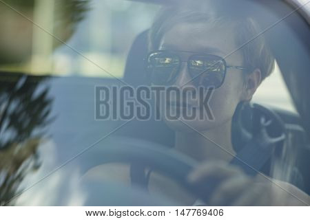 closeup of young Chinese beauty sitting behind windshield