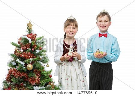 Children holding christmas cake pop dessert in shape of new year tree balls and snowman. Isolated over white background. Christmas tree. Copy space.
