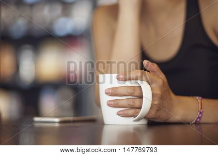 closeup of Chinese woman holding mug in coffee shop