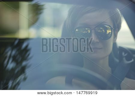closeup of young Chinese woman driving behind windshield