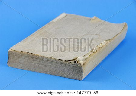 old dirty book isolated on blue background