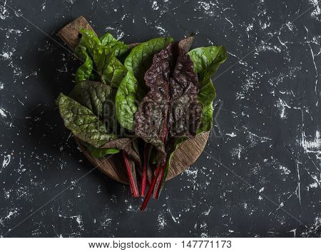 Fresh swiss chard or mangold on a wooden cutting board on a dark background