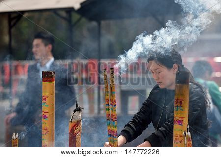 QIBAO CHINA - MARCH 20: Unidentified Chinese people pray in Qibao Temple on March 20 2016 in Shanghai China. Qibao is a historic scenic town located in Minhang District Shanghai China