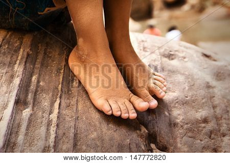 Young boy sitting on rock closeup of barefeet