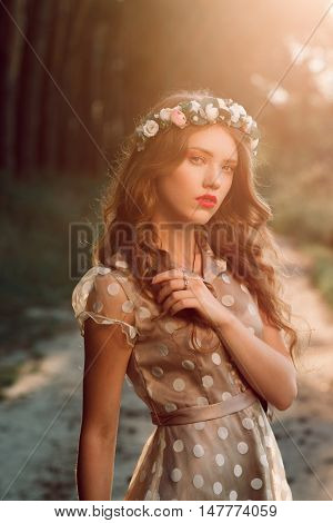 Attractive girl in wreath posing in forest. Beautiful fashion woman meet sunset in country, free space. Natural hair care, unity with nature concept