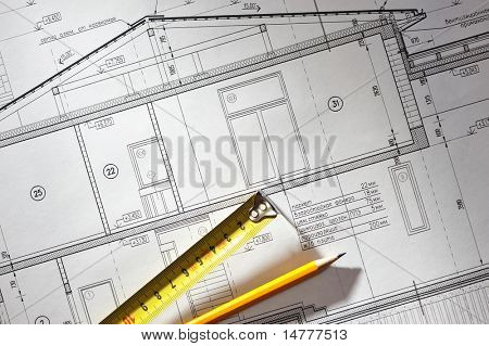 Pencil and tape meausure over house plan blueprints