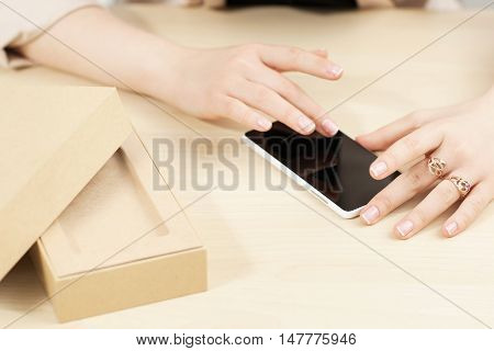Woman using new smartphone near carton box. Female hands testing touch screen of resent gadget. Modern technology presentation, online shopping concept