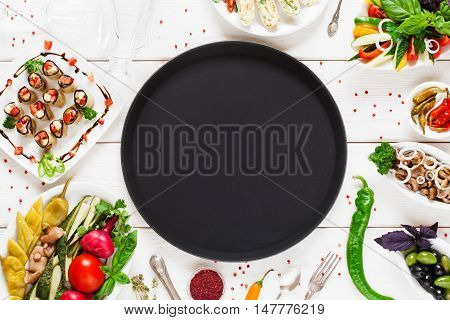 Black empty plate surrounded by food, void. Dark round dish on table with different snacks variety. Cuisine, menu, food concept