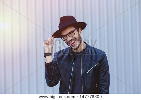 Attractive man wearing a leather jacket and hat in the city