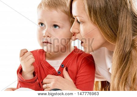 Portrait of a joyful mother and her baby son in the bed on white background