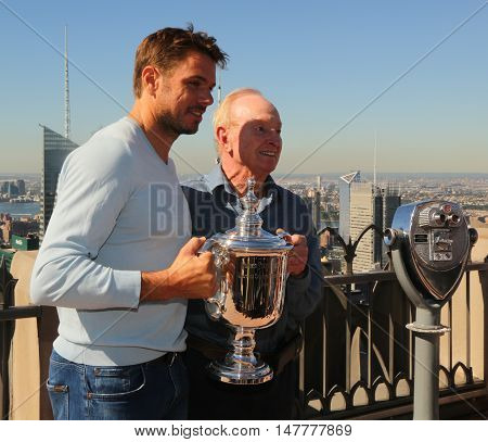 NEW YORK - SEPTEMBER 12, 2016: Grand Slam champions Stanislas Wawrinka (L) and tennis legend Rod Laver posing with US Open trophy on the Top of the Rock Observation Deck at Rockefeller Center in NY