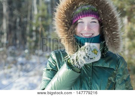 Cheerful young woman in winter forest is holding stainless steel thermos flask tourist cup outdoors poster