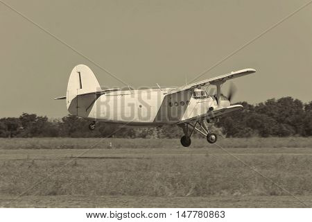 Old biplane takeoff from the rough airstrip black and white image