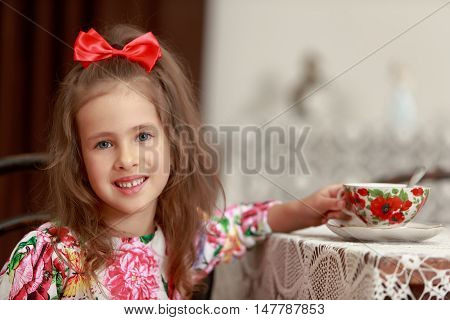 Gentle little girl with a long ponytail down to his shoulders, and a red bow on her head, in a beautiful summer dress. covered with a lace crocheted tablecloth. Beside her is a Cup of tea . close-up