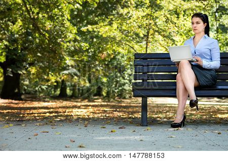 Sexy young businessgirl works with her laptop on the bench in the park
