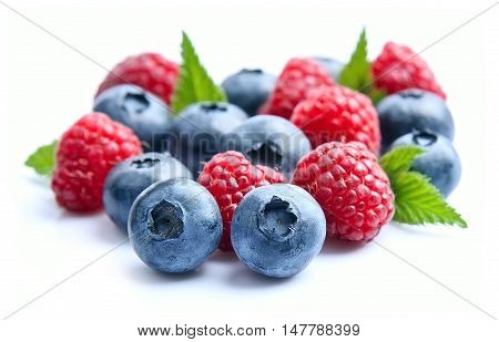 Sweet berry mix isolated on white background. Ripe raspberry and blueberries.