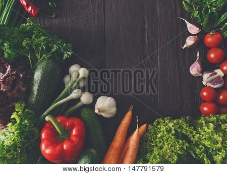 Border of fresh organic vegetables on wood background. Healthy natural food on rustic wooden table with copy space. Italian cuisine cooking ingredients top view, soft toning