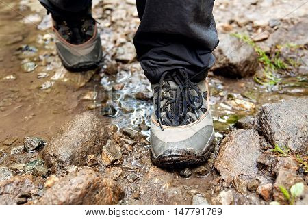 Hiking shoes on hiker outdoors walking crossing river creek. Woman on hike trekking in nature. Closeup of female hiking shoes in action. Trekking shoes.