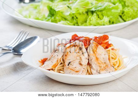 pan fried chicken breast on rich tomato pasta