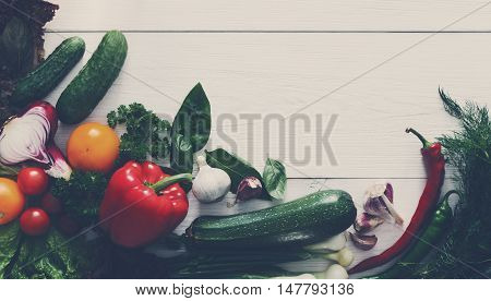 Bottom line border on white wood for menu or recipe, fresh organic vegetables and greens background. Healthy natural food on wooden table with copy space. Cooking ingredients top view, soft toning