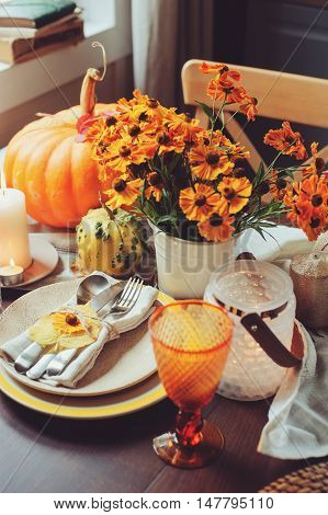 autumn traditional seasonal table setting at home with pumpkins candles and flowers