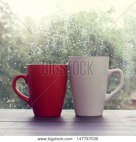 red and white cup standing on the wooden table outside when the rain drips / warming drink in the autumn weather