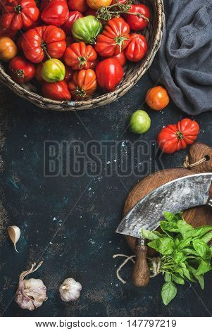 Fresh colorful ripe heirloom tomatoes in basket, basil leaves, garlic, herb chopper knife for cooking over grunge dark plywood background. Top view, copy space. Harvest vegetable cooking conception.