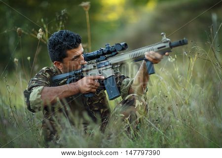 Man of Arab nationality in camouflage with a gun for trap shooting aiming at a target